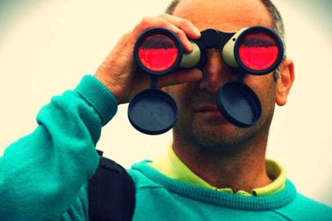 Homem olha através de binóculo